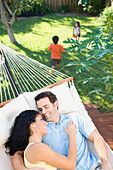 Couple relaxing in hammock with children playing in background