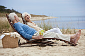 Caucasian couple laying on lounge chairs on beach
