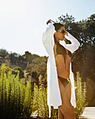 Hispanic woman in bikini putting on robe