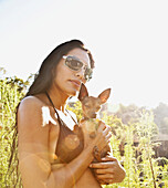 Hispanic woman in bikini holding dog