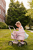 Caucasian girl dressed as princess playing with stroller
