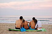 Teenage couples sitting on surfboard on beach