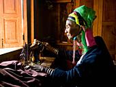 Burmese woman wearing neck rings at sewing machine