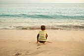 Mixed race boy squatting on beach playing