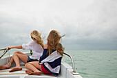 Caucasian girls sitting on boat