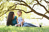 Caucasian mother and son relaxing in park
