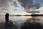 Caucasian woman meditating on wooden dock in still lake