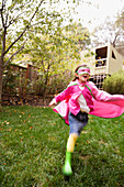 Middle Eastern girl wearing cape and mask running in backyard
