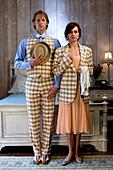 Elegant couple standing in bedroom in evening clothes