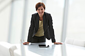 Caucasian businesswoman leaning on conference room table