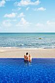 Couple relaxing in infinity pool