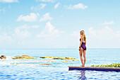 Caucasian woman walking by infinity pool