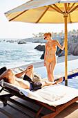 Couple relaxing at poolside overlooking ocean