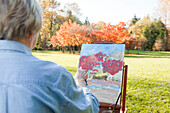Senior woman painting outdoors