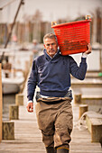 Caucasian fisherman carrying basket on dock