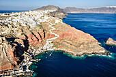 Aerial view of city built on rocky coastline, Oia, Egeo, Greece