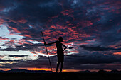 Silhouette of boy with walking stick under sunset sky, Nyangaton, Ethiopia