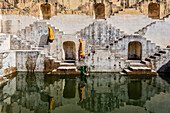 Women in saris carrying water at step well, Jaipur, Rajasthan, India