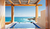 Window overlooking infinity pool and ocean