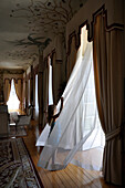 Young Girl Standing in Front of Open French Doors While Wind is Blowing Sheer Curtains in Grand Hotel Sitting Room