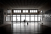 Silhouette of Woman Sitting at Desk in Art Gallery