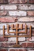 Metal Menorah Symbol on Brick Wall