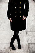 Woman Wearing Black Coat with Gold Buttons and Black Boots, Close-Up View From Torso-Down