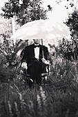 Seated Man in Tuxedo Holding Umbrella