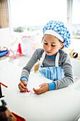 Boy in Chef Hat and Apron Writing Note with Crayon
