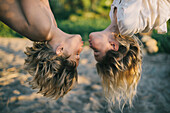 Young Boy and Girl Hanging Upside Down About to Kiss