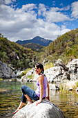PESCADERO, BAJA CALIFORNIA SUR, MEXICO. A portrait of a young woman sitting on a rock in a small stream.