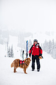 STEVEN'S PASS, WASHINGTON, USA. Court Wing, a legendary ski patroller at Steven's Pass, WA with his dog on a snowy day.