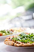 BIRMINGHAM, ALABAMA, USA. Arugula piled high on a small pizza at a high end restaurant.