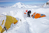 A mountain ranger is digging out tents after a snowstorm covered them during the night in 14k camp on Mount McKinley, Alaska.     Climbers are advised to spare no expense on a expedition-quality tent as it can mean the difference between life and death du