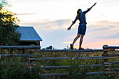 Woman balances on a split rail fence on a ranch in Bozeman, MT in the summertime.