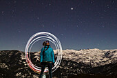 A woman skier looks up into the starry night sky in Montana's backcountry.