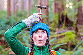 Woman makes a silly face and holds a mushroom on top of her head in the Hoh Rainforest, WA