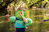 Toddler boy with floatie and goggles spies camera through net in creek at Bidwell Park, Chico, California.