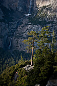 A female backpacker goes down a trail with Upper Yosemite Falls in the background in Yosemite National Park.