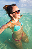 A young woman relaxes in shallow clear turquoise water while on vacation in Cayo Coco, Cuba.