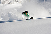 A man skiing powder on a beauitful sunny day in Utah