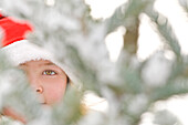 Young girl peering through snow covered Christmas Tree in winter, UK.