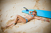 Beautiful surfer girl relaxing on the sand beach.