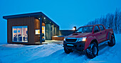 Customised 4x4 pick up truck parked outside of a cottage in the winter in Laugar in north Iceland during a snowstorm