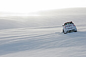 customised SUV driving through snow close to Einistadir in North Iceland