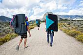 Guys walk with climbing pads through Idaho wilderness