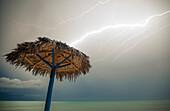 Lightning strikes a beach umbrella made of palm branches on Playa La Jaula beach, Cayo Coco, Cuba.