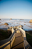The morning sun shines on a long wooden staircase that leads down to Bandon Bay on the Oregon Coast.