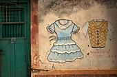 A painting of a dress and a shirt decorate a wall in a clothing store in Santa Elena,Yucatan, Yucatan Peninsula, Mexico