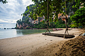 A wooden swing on the sand of Tonsai Beach in Krabi, Thailand with long tail boats in the background.